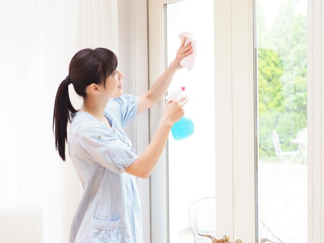 大きな窓を掃除する女性